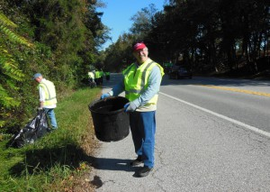 MET staffer picking up litter on a sunny day, which helps protect the environment and keeps scenic byways beautiful