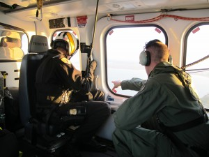 An NRP officer (right) directs the State Police helicopter flight team toward a target.