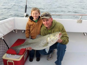 Captain Keith Allston Jr. and Junior Abell showcase a rockfish  caught during opening day aboard Rod Bender Charters out of Solomons. Photo by Ashley Abell.