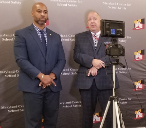 A behind the scenes shot showing the webinar setup. Dr. Tarik Harris and Michael Rudinski stand in front of a MCSS backdrop in front of a camera.